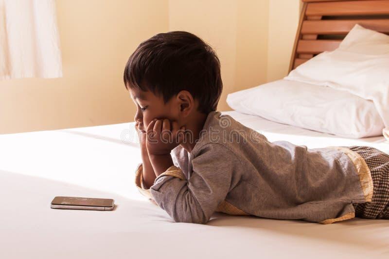 Chłopiec kłaść na łóżkowej sztuki mądrze telefonie obrazy royalty free