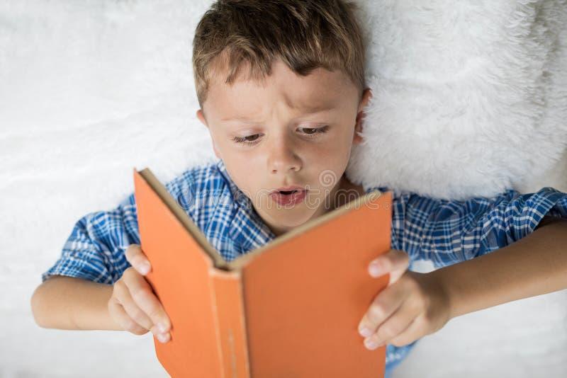 Chłopiec kłama na czytaniu i łóżku książka zdjęcia royalty free