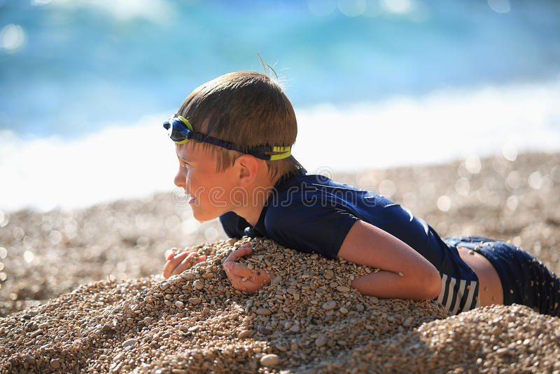 Chłopiec kłama na otoczak plaży po pływać zdjęcia stock