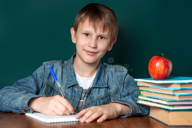 Chłopiec Kaukaski pojawienie na tle zarząd szkoły Obok on jest sterta notatniki i podręczniki, jabłko zdjęcie stock