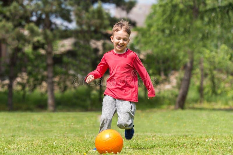 Chłopiec kopania piłka obrazy stock
