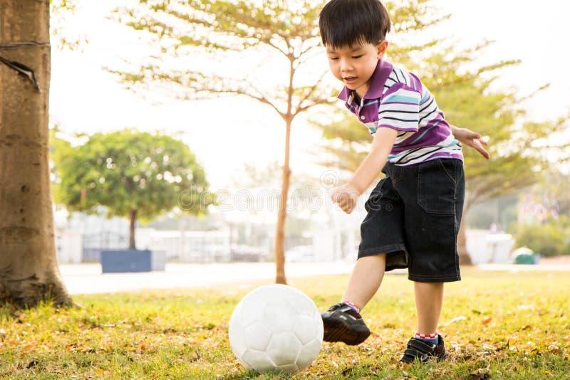 Chłopiec kopnięcia piłka przy parkiem w wieczór obraz royalty free