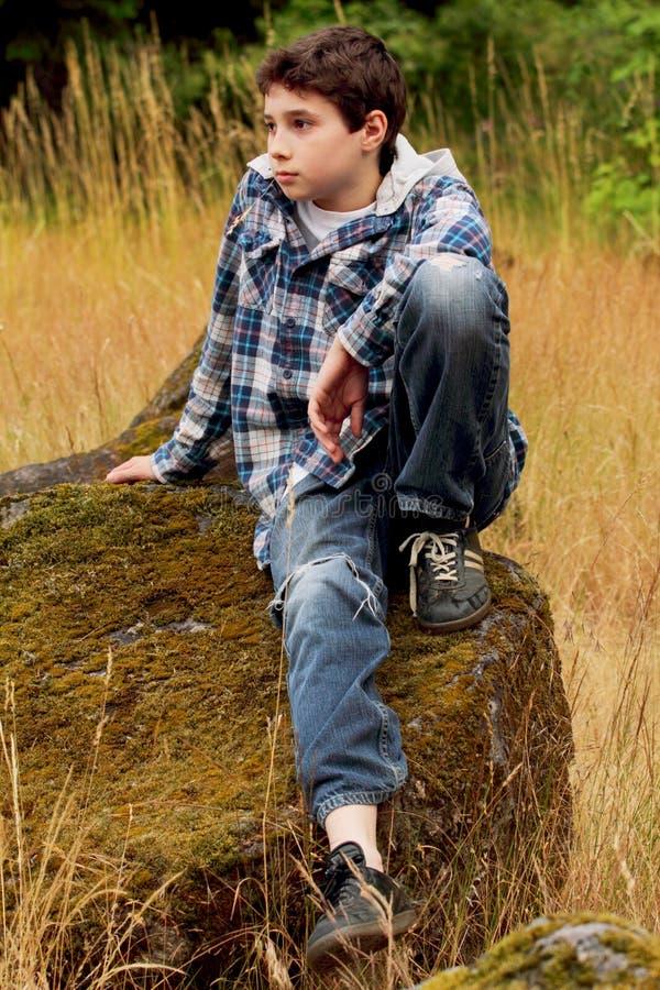 chłopiec kraju preteen skały obsiadanie fotografia stock