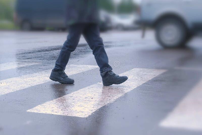 Chłopiec krzyżuje drogę przy zwyczajnym skrzyżowaniem w deszczu Nogi zakończenie fotografia stock