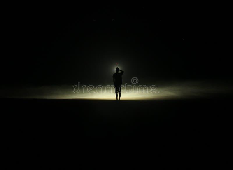 Chłopiec który stoi w plaży w Ciemnej nocy obrazy stock