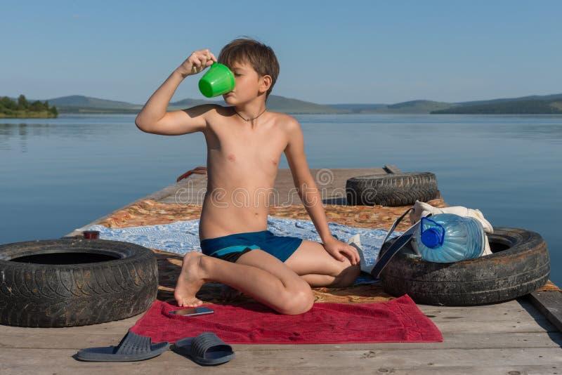 Chłopiec 11 lat lasuje jego pragnienie z wodą od kubka, siedzi na drewnianym molu, przeciw tłu jezioro na a zdjęcie stock
