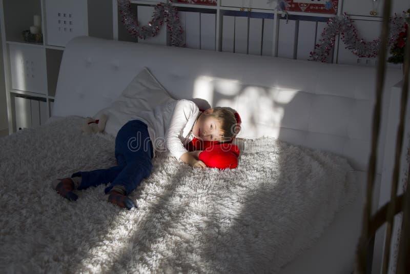 Chłopiec leży na białym łóżku zdjęcia stock