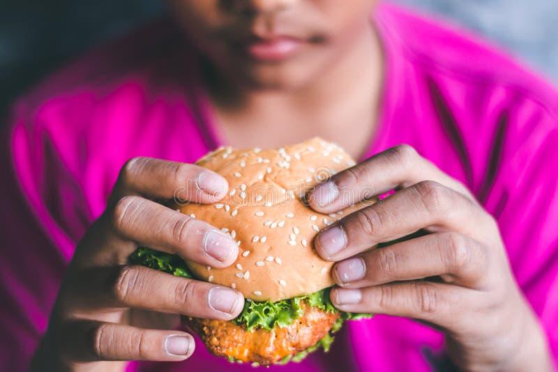 Chłopiec lubią jeść hamburgery zdjęcia royalty free