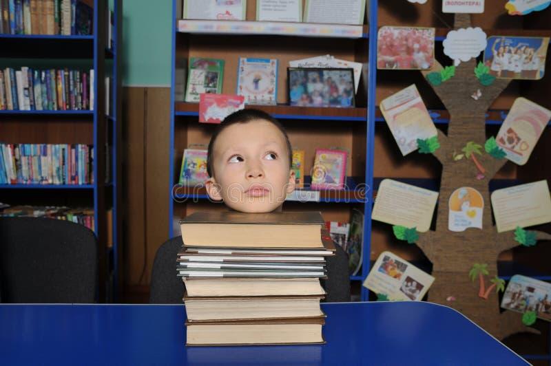 Chłopiec lying on the beach myśląca głowa na stosie książki w bibliotece, kładzenie głowa na stosie książka fotografia royalty free