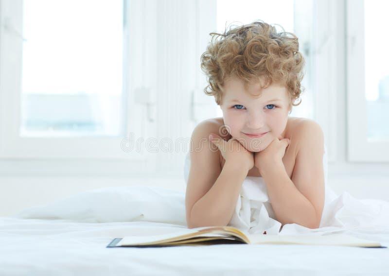 Chłopiec lying on the beach na łóżkowej czytelniczej książce w domu Czytać w łóżku jest złym przyzwyczajeniem fotografia royalty free