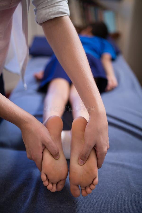 Chłopiec lying on the beach na łóżku podczas gdy odbiorczy nożny masaż od młodego żeńskiego terapeuta obraz royalty free