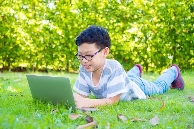 Chłopiec lying on the beach na trawy polu i używać laptopie zdjęcie royalty free