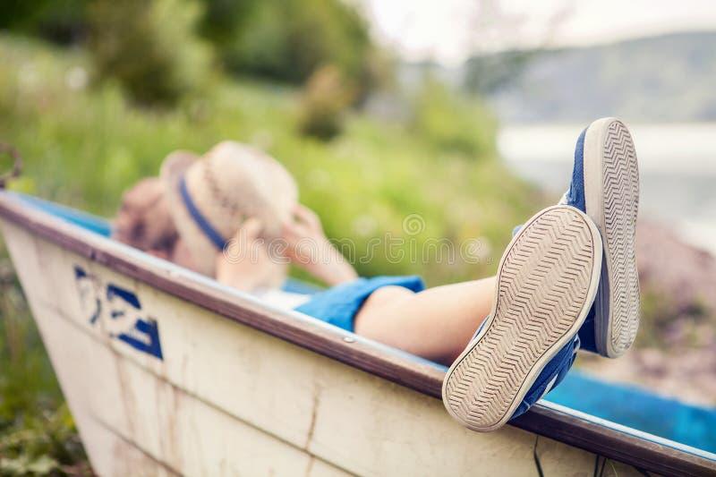 Chłopiec lying on the beach w starej łodzi w jeziornym wybrzeża zakończeniu w górę wizerunku fotografia stock