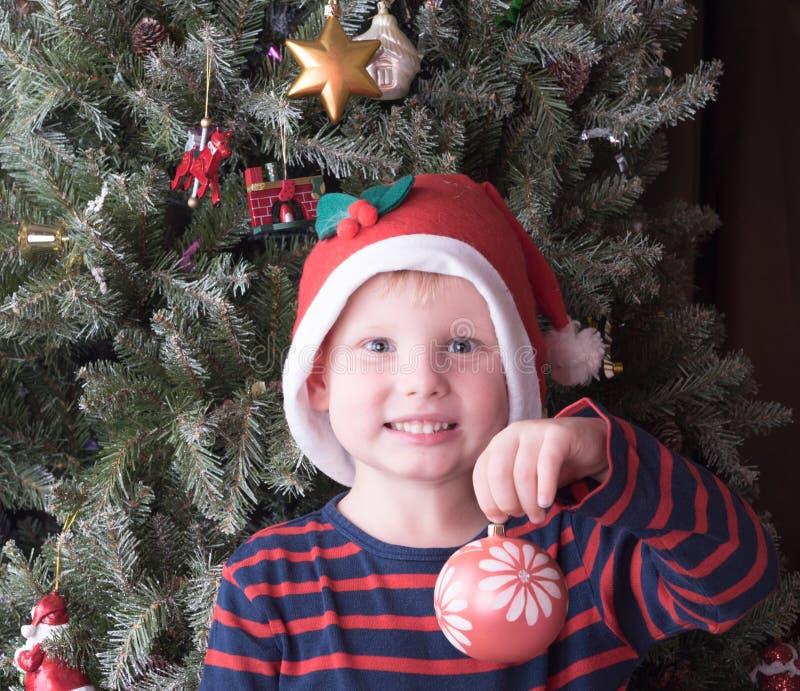 Chłopiec ma bożych narodzeń ono uśmiecha się i piłkę fotografia royalty free