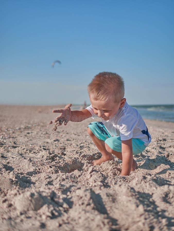 Chłopiec ma na plażowej zabawie z piaskiem Dziecko bawić się na nadmorski w latach Lata Spoczynkowy pojęcie Szczęśliwy zdjęcia stock