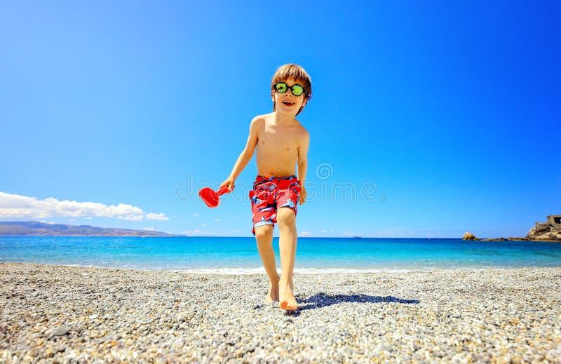 Chłopiec ma zabawę przy plażą na wakacje Żartuje być ubranym okulary przeciwsłonecznych i uśmiechniętego bieg w kierunku kamery obraz stock