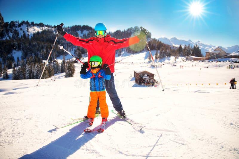 Chłopiec ma zabawę z jego atrakcyjnym ojcem podczas narciarstwa w Alps zdjęcia royalty free