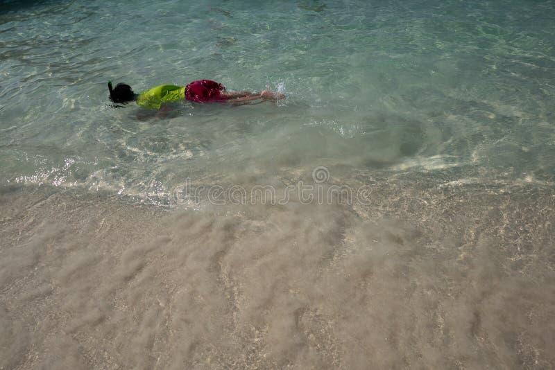 Chłopiec ma zabawę z snorkeling przy płycizna jasnego morzem fotografia stock
