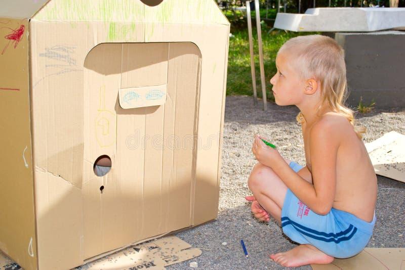 Chłopiec maluje karton zdjęcia royalty free