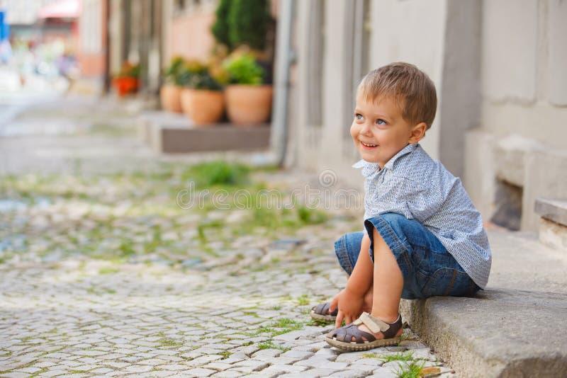 chłopiec miasta próg trochę siedzi ulicę obrazy stock