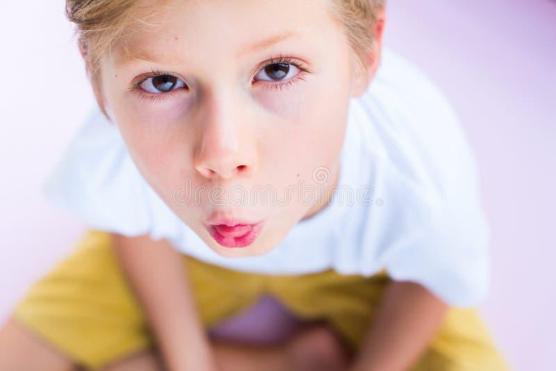 Chłopiec mienia kwiatu usta menchii tło fotografia stock
