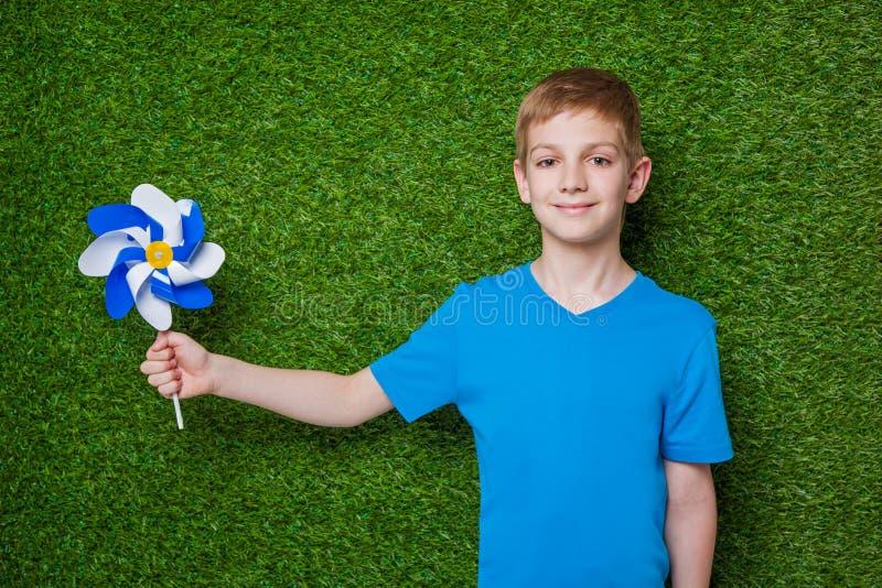 Chłopiec mienia pinwheel nad zieloną trawą fotografia stock