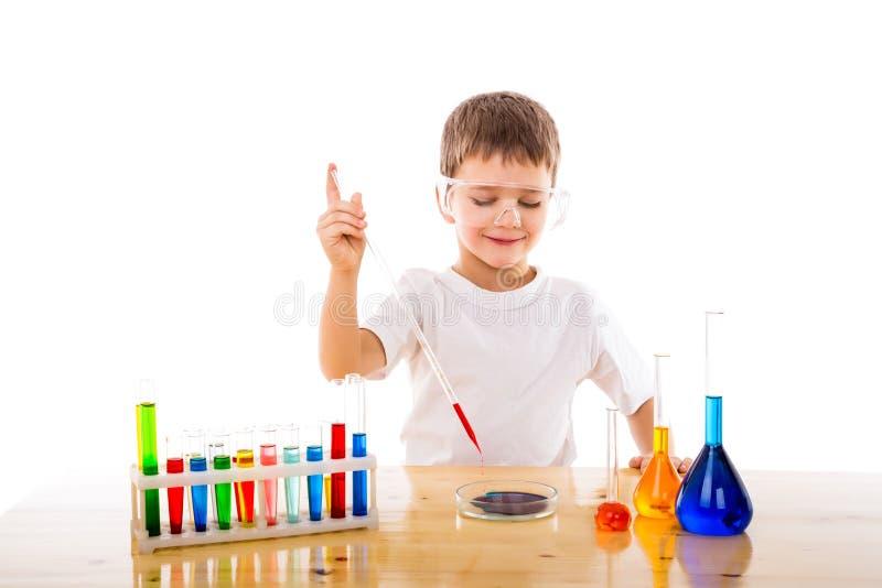 Chłopiec miesza substancje chemiczne w lab zdjęcie royalty free