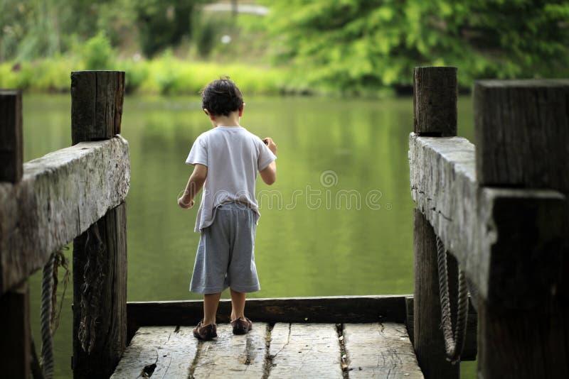 Chłopiec miotania kamienie jezioro zdjęcia stock