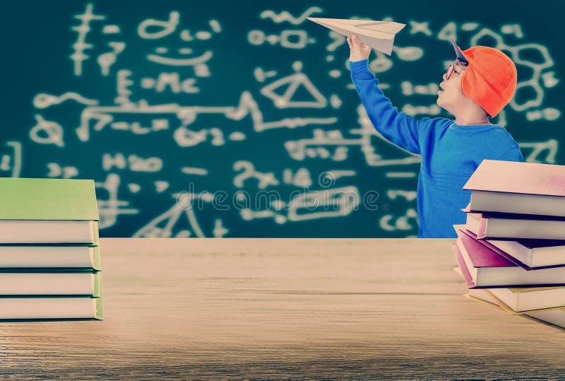 Chłopiec miotania papier hebluje i drewniany stół z książkową stertą, z zdjęcia royalty free