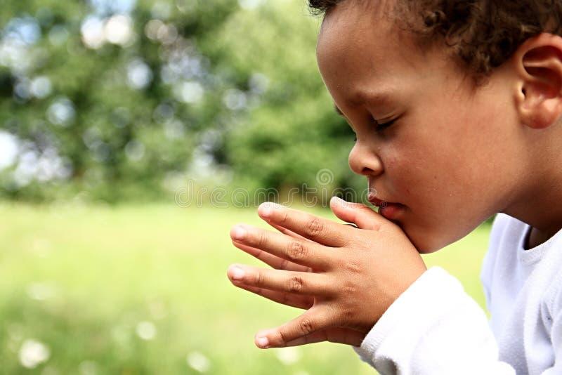 Chłopiec modlenie z zamkniętymi oczami fotografia royalty free
