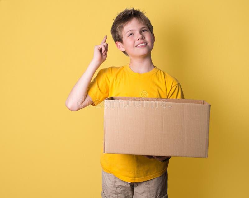 Chłopiec myślący mienie pudełko na żółtym tle Myśl z th obraz stock