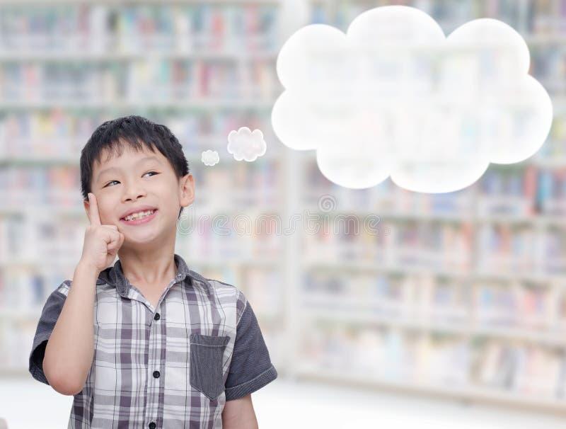 Chłopiec myśl z bąblami w bibliotece fotografia stock