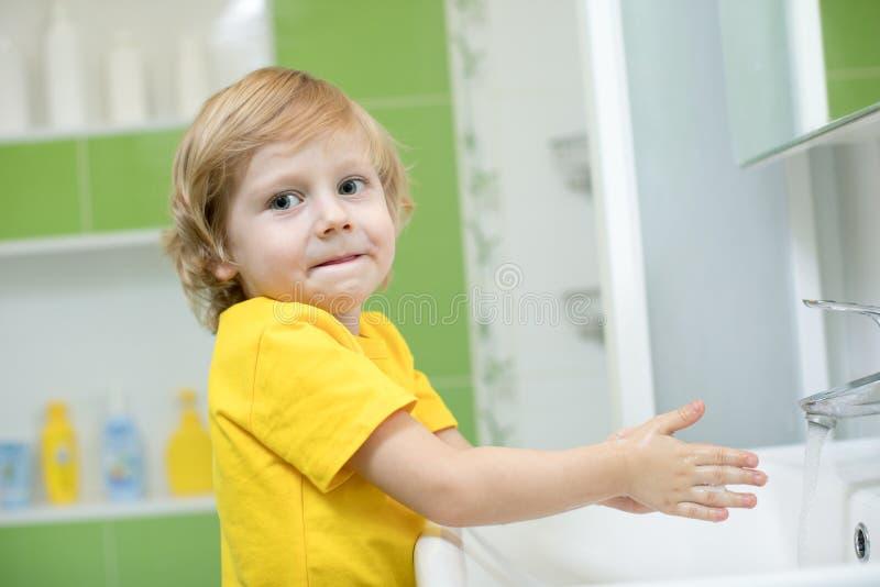 Chłopiec myje jego ręki w łazience obrazy royalty free