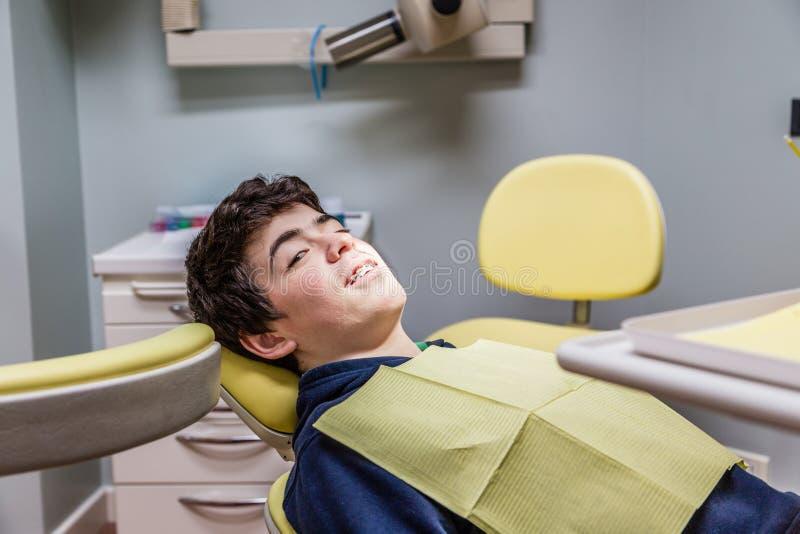 Chłopiec na dentysty krzesła seansu brasach obraz royalty free