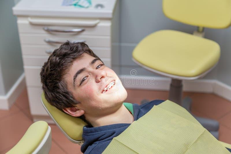 Chłopiec na dentysty krzesła seansu brasach zdjęcia stock
