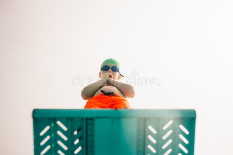 Chłopiec na nurkowej platformie przy basenem obrazy stock