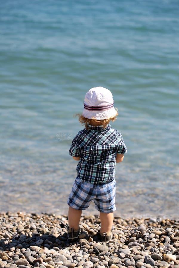 Chłopiec na otoczak plaży obraz royalty free