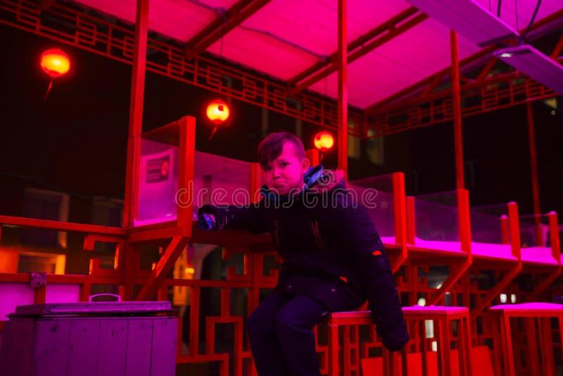 Chłopiec na ulicie w neonowym oświetleniu Miasto w neonowym świetle obrazy stock