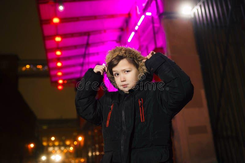 Chłopiec na ulicie w neonowym oświetleniu Miasto w neonowym świetle fotografia stock
