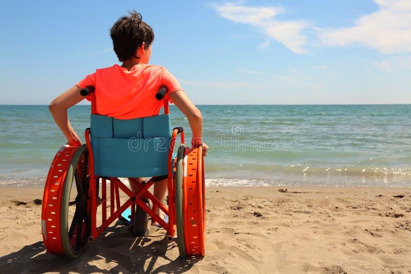 Chłopiec na wózku inwalidzkim morzem zdjęcie royalty free