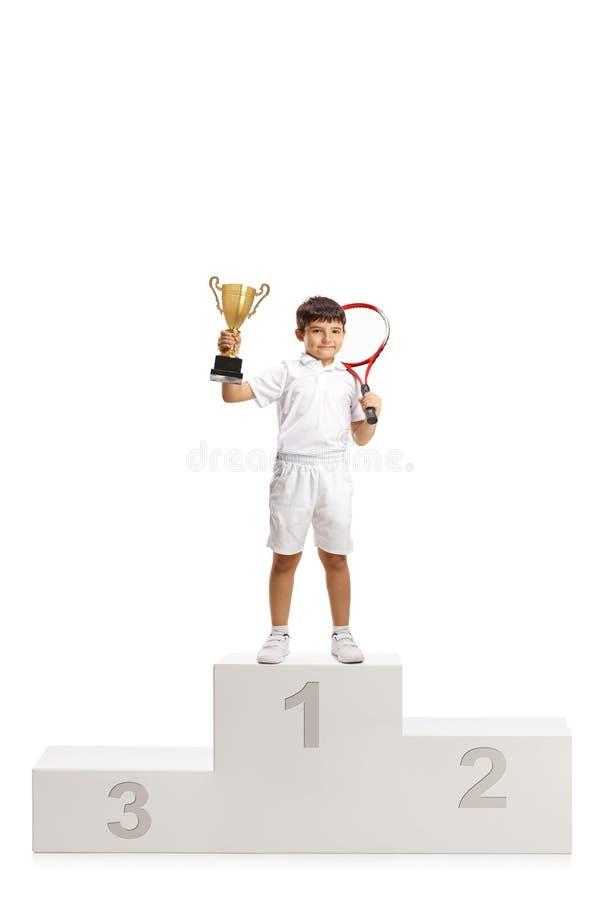 Chłopiec najpierw umieszcza tenisowego zwycięzcy z trofeum filiżanki pozycją na zwycięzcy piedestale zdjęcie stock