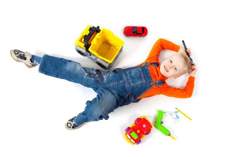 Chłopiec naprawia jego zabawkarskiego samochód zdjęcia stock