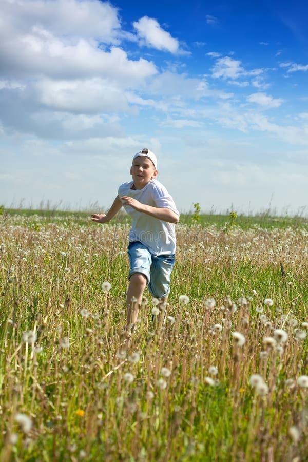 chłopiec nastolatek łąkowy działający obrazy stock