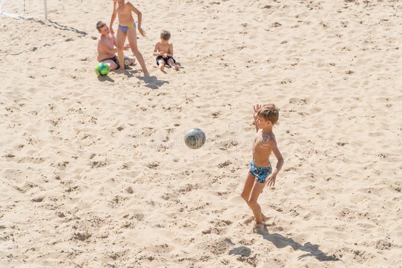 Chłopiec nastolatkowie bawić się piłkę nożną na plaży obraz royalty free