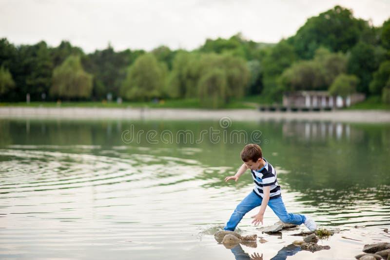 Chłopiec niegrzeczna, śmieszny, spadek, potknięcie wodny, mokry, jeziorny, niebezpieczeństwo, gubi równowagę, dzieciak obraz royalty free