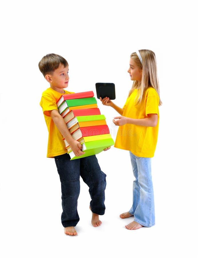 Chłopiec niesie ciężkie książki, dziewczyna pokazuje on ebook zdjęcie royalty free