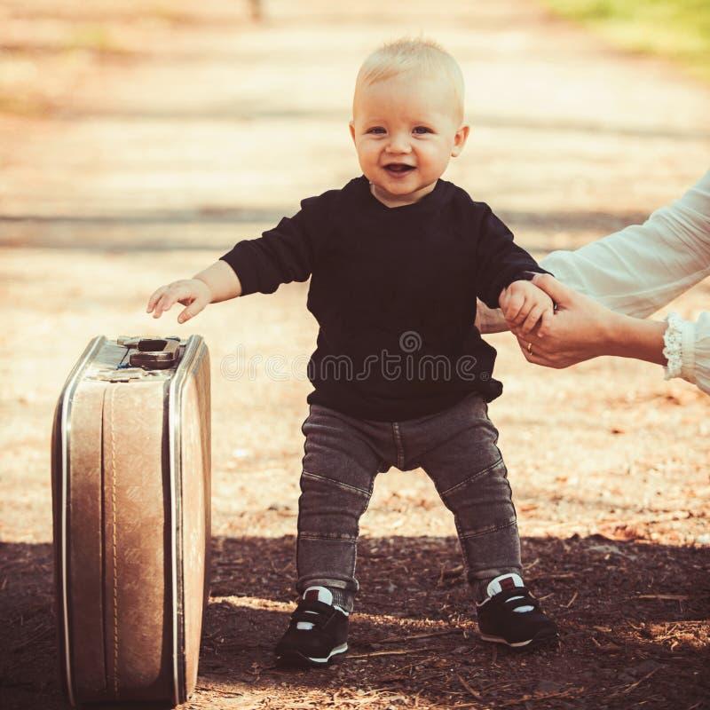 Chłopiec niesie walizkę na naturalnym krajobrazie Chłopiec podróż dla wakacje z retro torbą z matki ręką zdjęcie stock