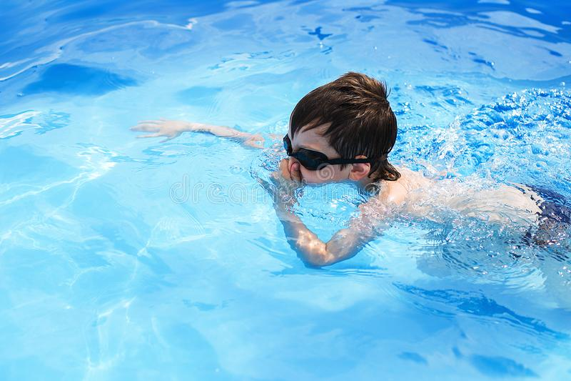 Chłopiec nurkuje w basenie z pływackimi szkłami W basenie ch?opiec p?ywania obraz royalty free