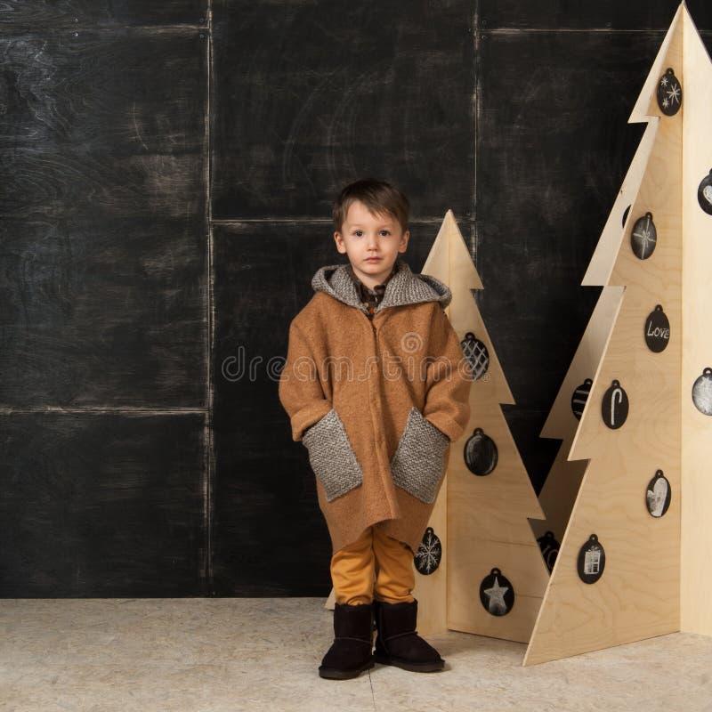 Chłopiec obok dekoracyjnych choinek obraz stock