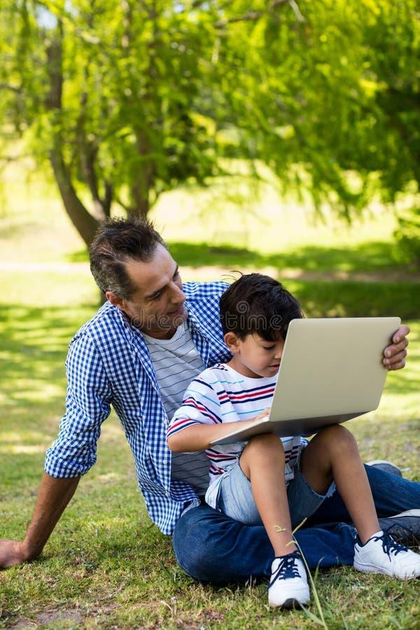 Chłopiec obsiadanie na jego ojcuje podołek i używać laptop w parku fotografia royalty free